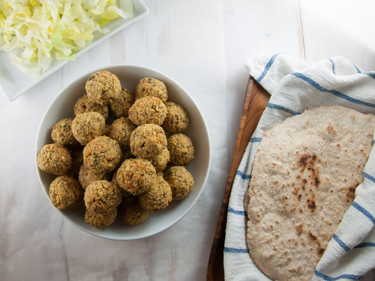 Huge Batch of Oven-Baked Falafel with flatbread and salad on the side