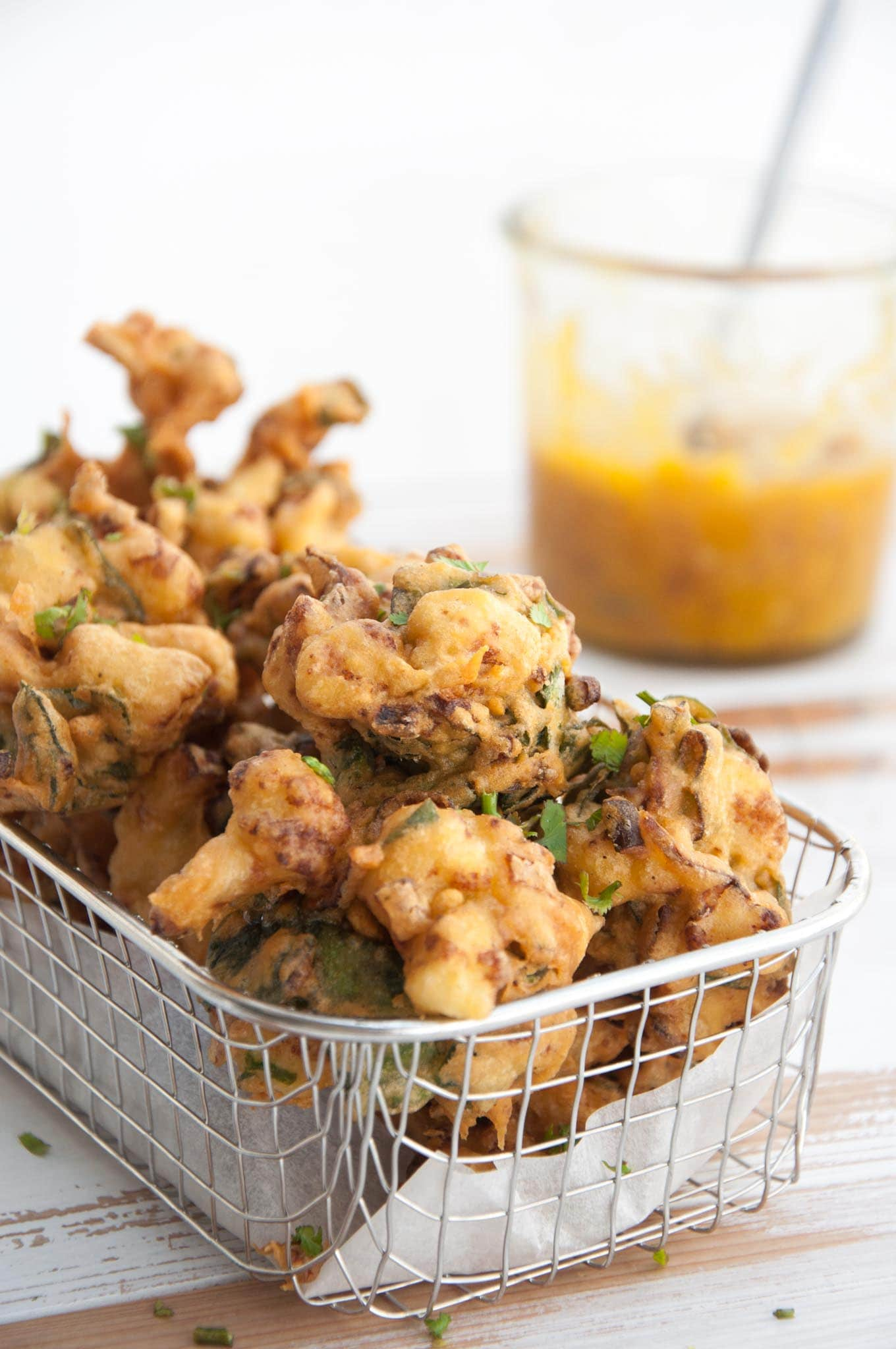 Vegetable Pakoras in a basket with mango chutney in the background
