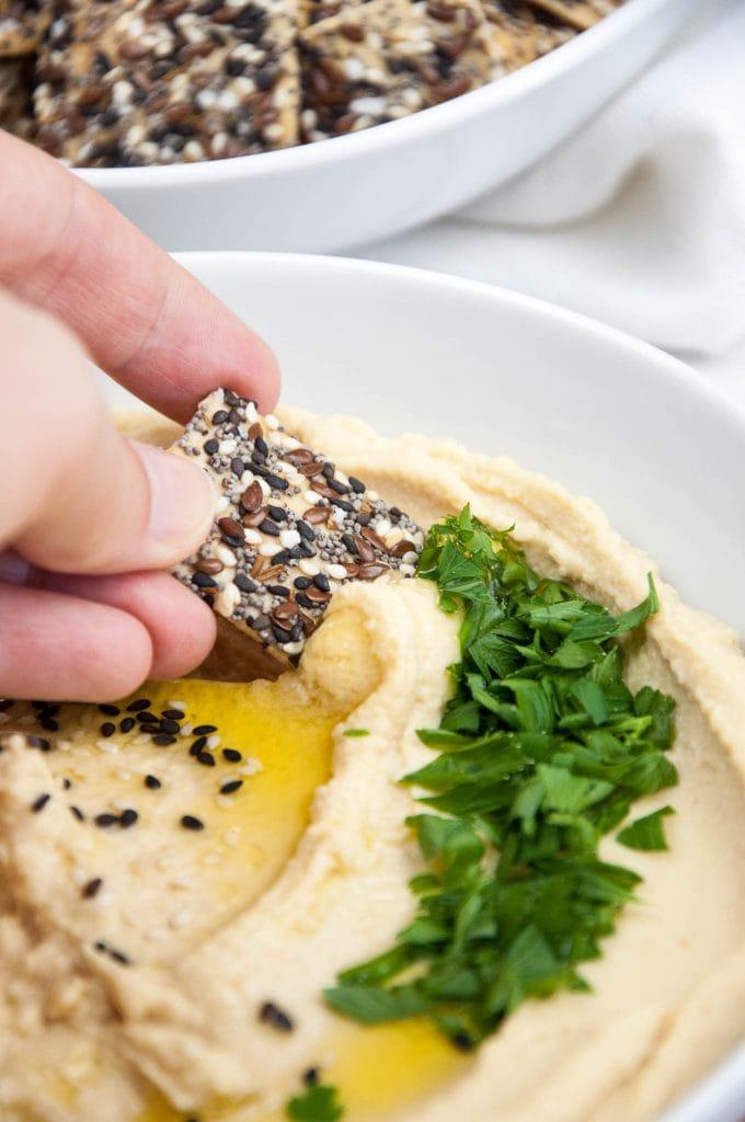 Cracker dipping into Homemade Hummus   ElephantasticVegan.com
