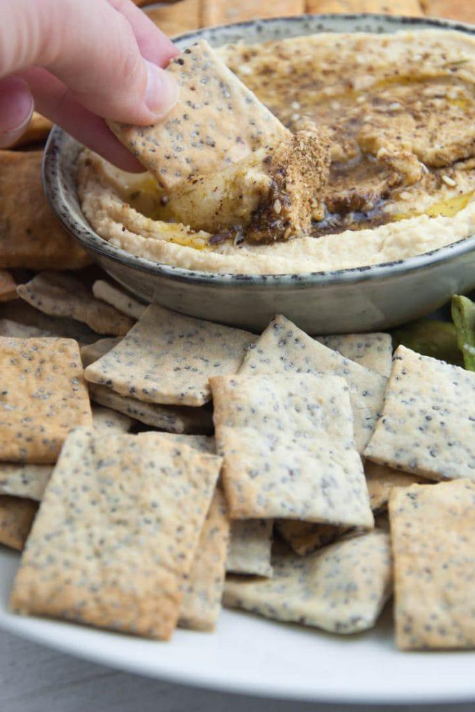 Vegan Poppy Seed Crackers dipped into Za'atar Hummus