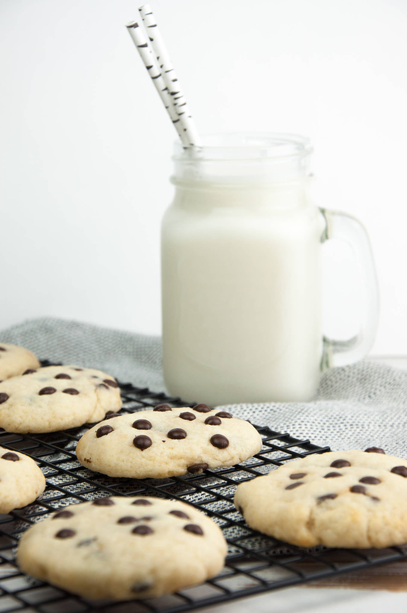 Soft Baked Vegan Chocolate Chip Cookies with plant-based milk in the background
