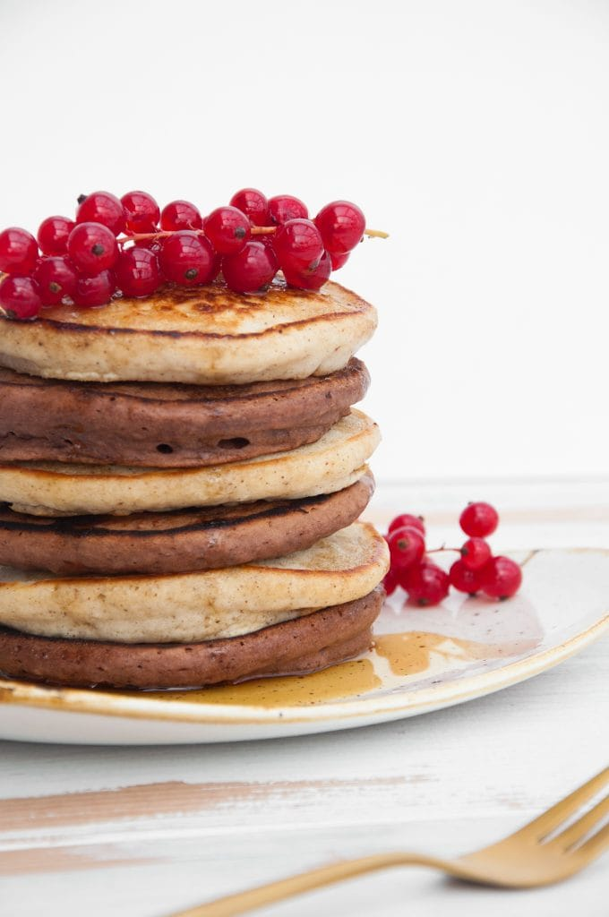 Vegan Cocoa and Vanilla Pancake Tower from the side, topped with red currant