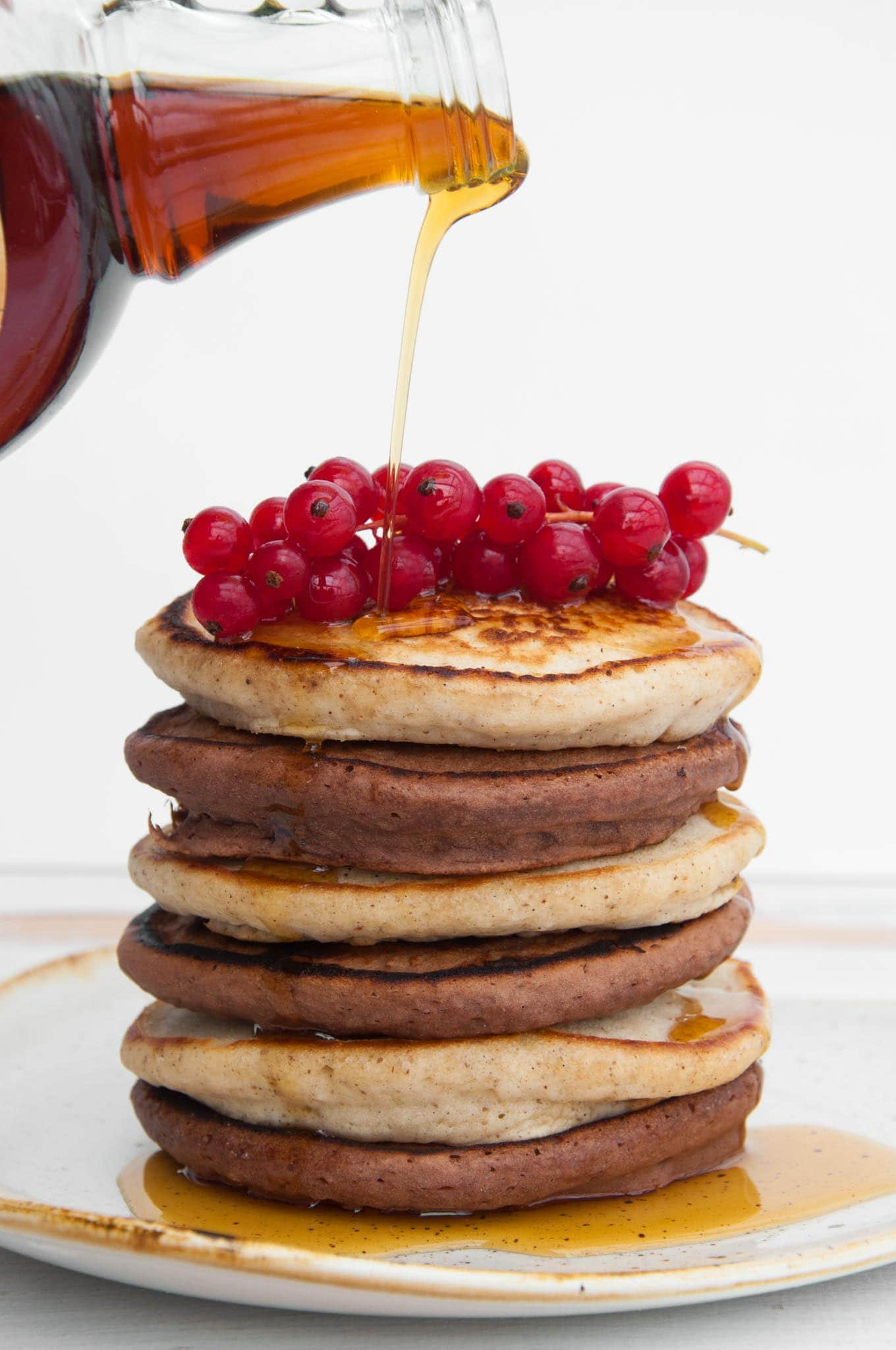 Vegan Cocoa and Vanilla Pancake Tower with maple syrup drizzling on top