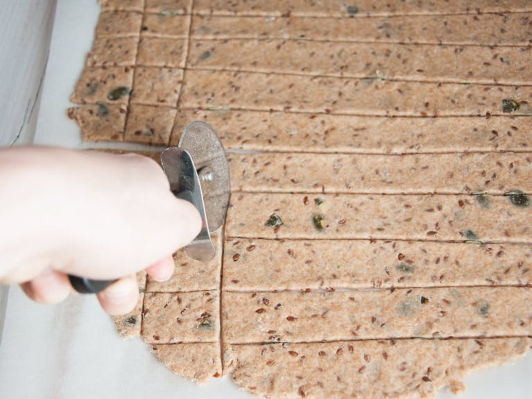 Cutting Whole Wheat Seed Crackers with a pizza cutter