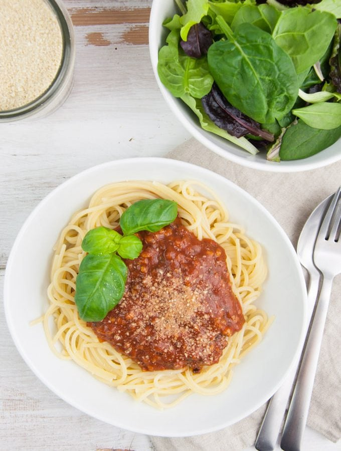 Spaghetti with vegan bolognese sauce, cashew parmesan and salad