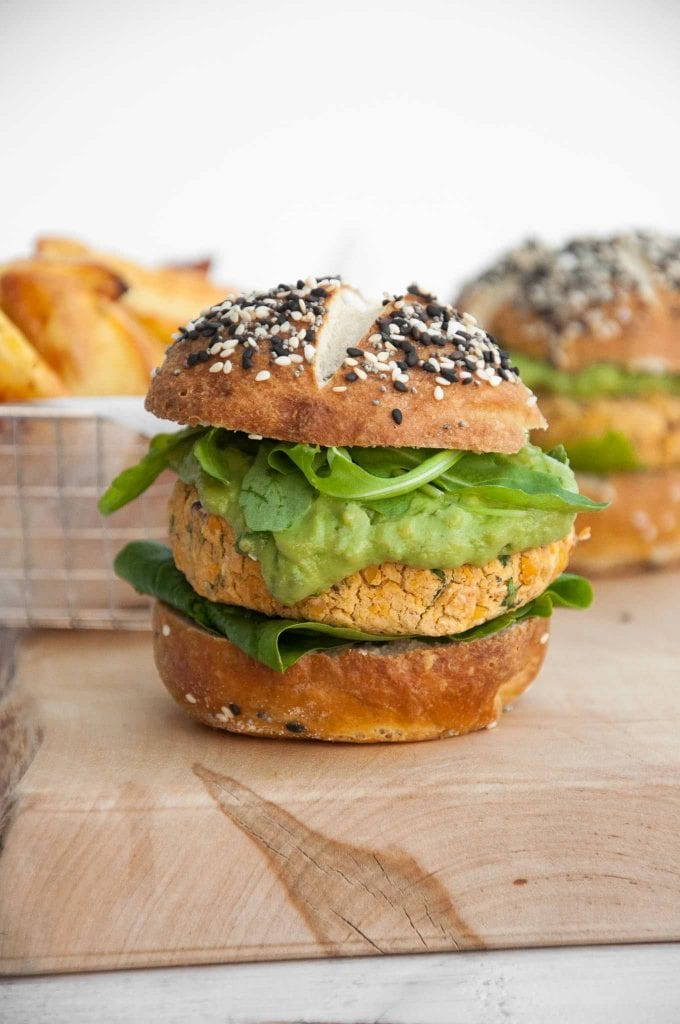 Vegan Falafel Burger with avocado sauce, arugula and spinach in pretzel buns