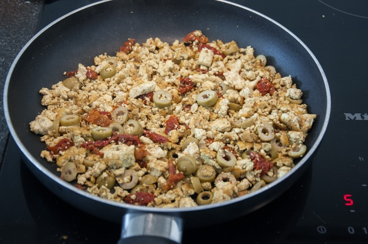 tofu scramble with olives and dried tomatoes in pan