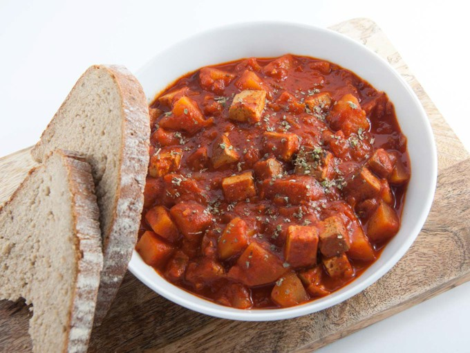 Vegan Goulash with smoked tofu and potatoes in a white bowl with bread to serve