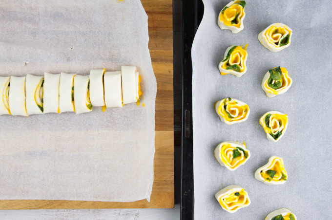 Sliced pinwheels on the left and pinwheels on a baking tray