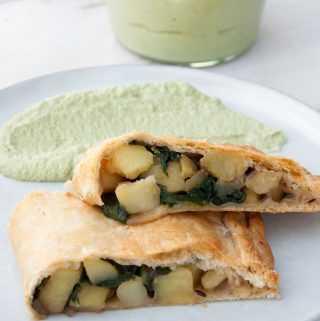 Vegan Potato and Spinach Strudel from the side with cilantro sunflower sauce in the background