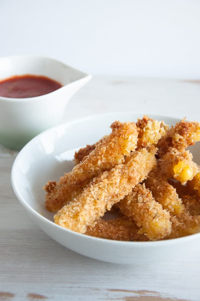 Vegan Cheese Sticks in a bowl with marinara sauce to serve