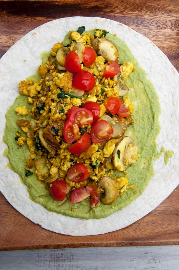 open-faced Mushroom Spinach Tofu Wrap consisting of tofu scramble, cilantro hummus, mushrooms, spinach and tomatoes