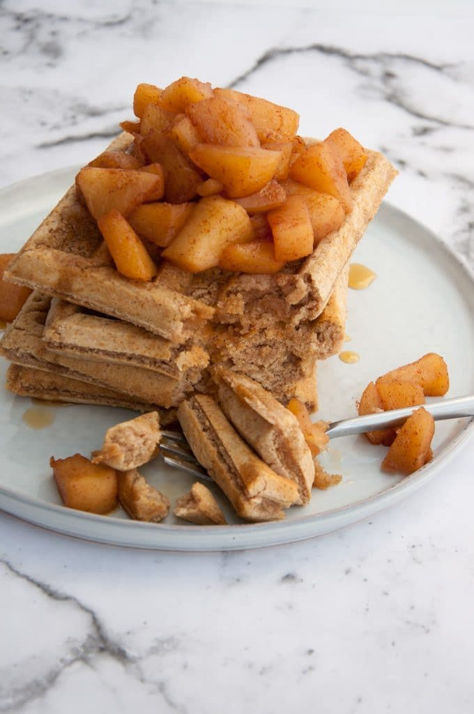 Vegan Cinnamon Waffles topped with warm Apple Sauce cut into with a fork