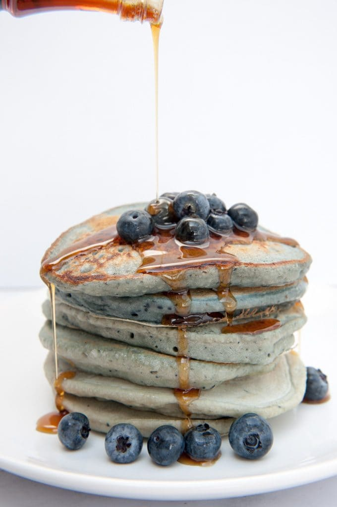Stack of Blue Pancakes drizzled with maple syrup