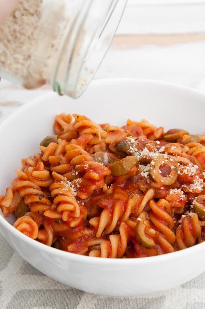 Sprinkling Almond Parmesan onto vegan Tomato Olive Pasta