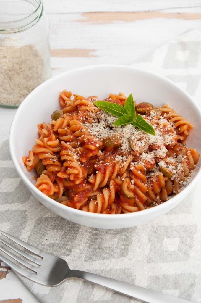 Pasta with tomato sauce and olives, garnished with fresh basil and almond parmesan