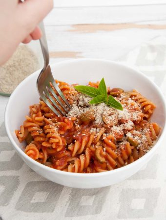 A fork digging into Tomato Olive Pasta