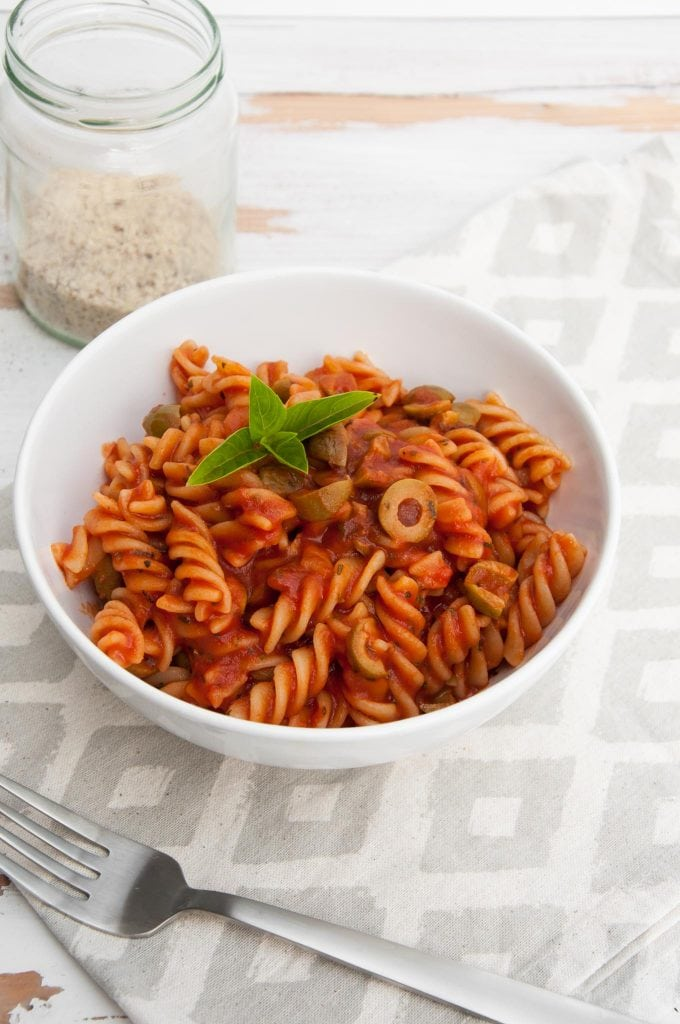 Pasta with tomato sauce and olives in a bowl with almond parmesan on the side