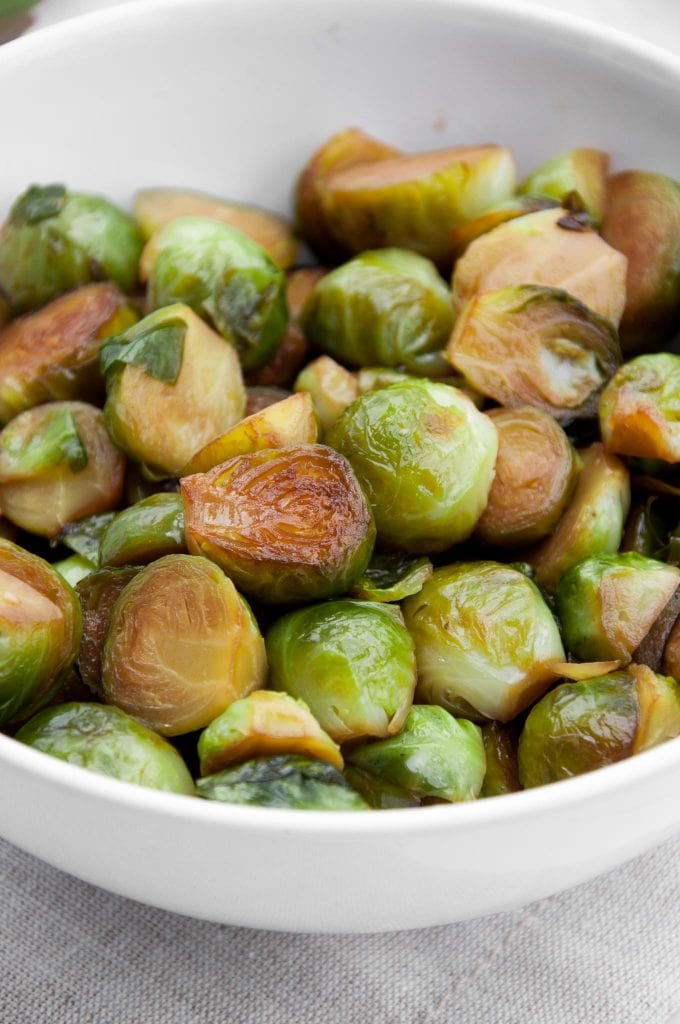 Pan-Roasted Brussels Sprouts in Soy Sauce in a white bowl - closeup