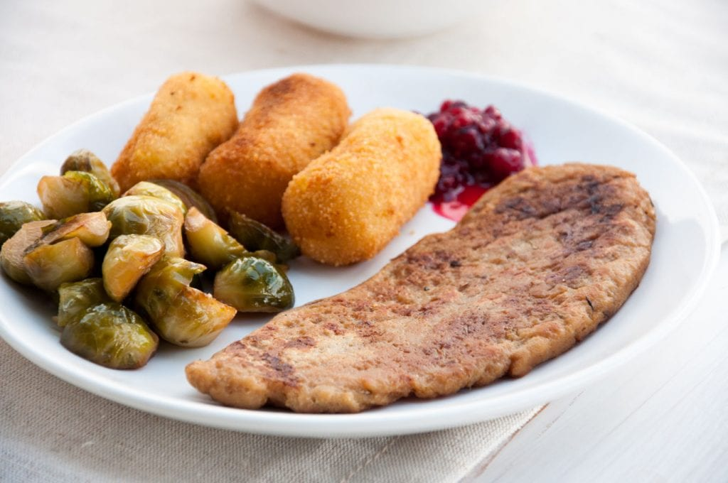 Vegan Seitan Steak on a plate with brussels sprouts, potato croquettes and lingonberry jam