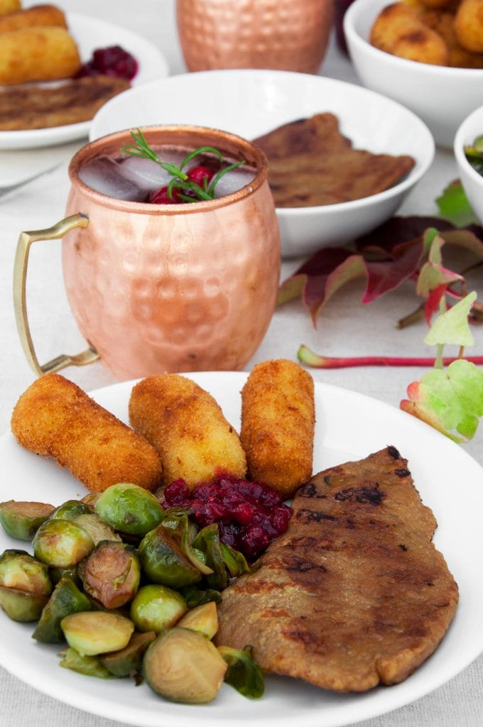 Vegan Thanksgiving Plate with seitan steaks, brussels sprouts, potato croquettes, lingonberry jam and cranberry moscow mule