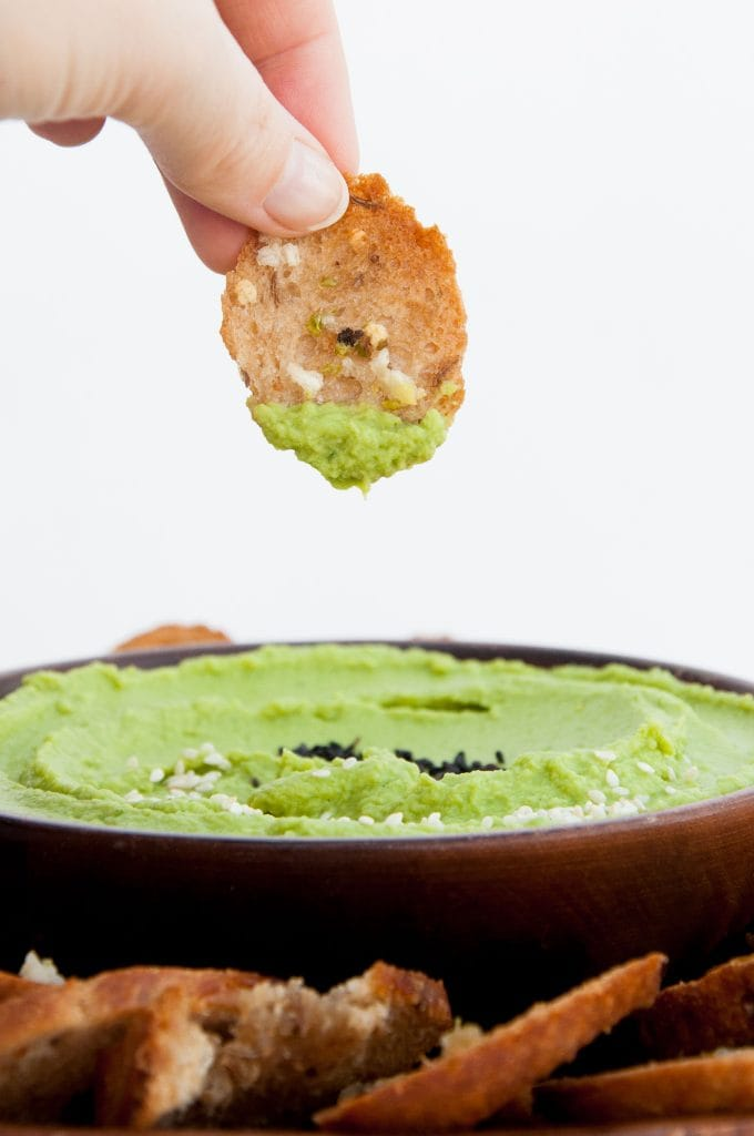 Crispy Bread Chips dipped in spinach hummus