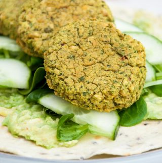 Spinach Falafel, cucumber, salad and mashed avocado on a tortilla