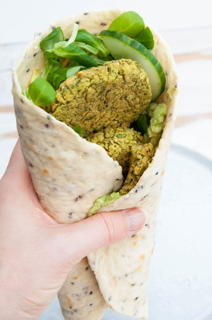Green Goddess Wrap - Tortilla with salad, cucumber, avocado and spinach falafel in a hand