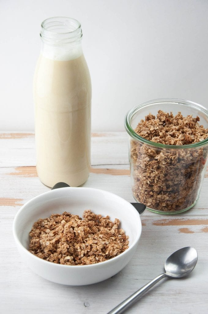 Vegan Gingerbread Granola in a bowl and glass jar with almond milk in the back