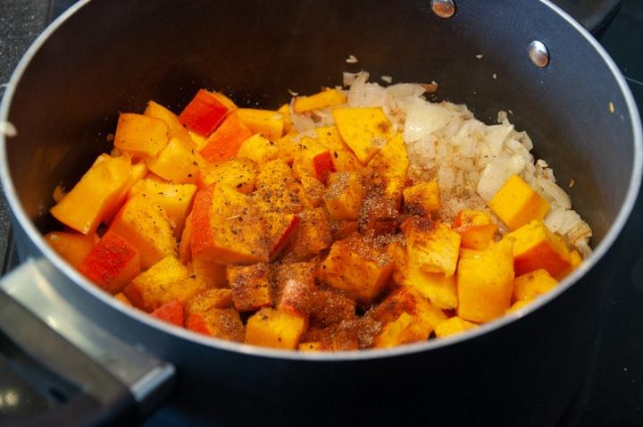 pumpkin, spices, onion, garlic in pot