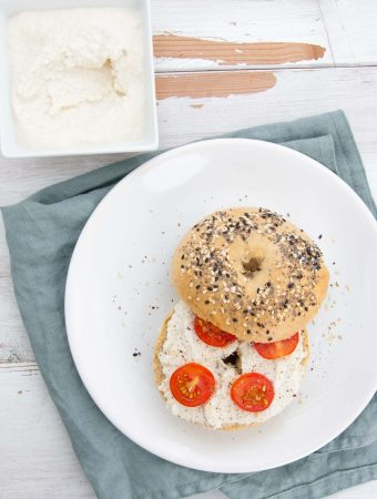 Almond Cream Cheese on a bagel with cherry tomatoes and cracked pepper