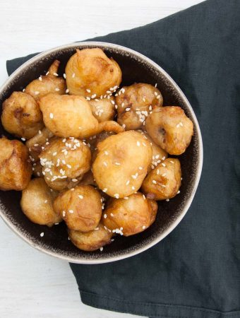 Vegan Banana Fritters coated in maple syrup and sprinkled with sesame seeds