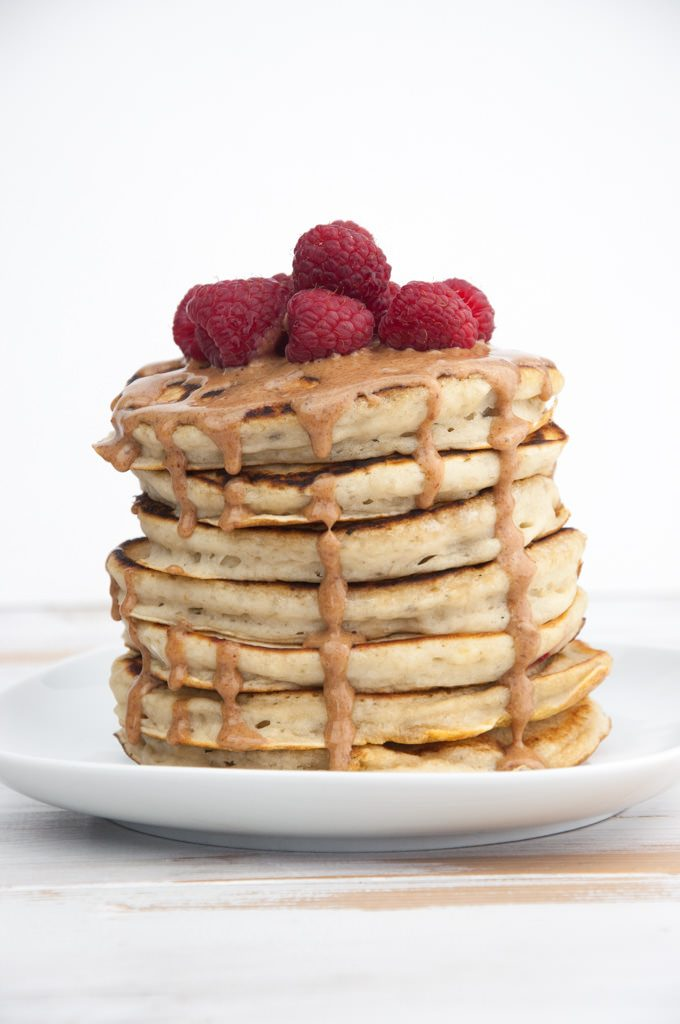 Fluffy Vegan Banana Pancakes topped with almond butter and raspberries