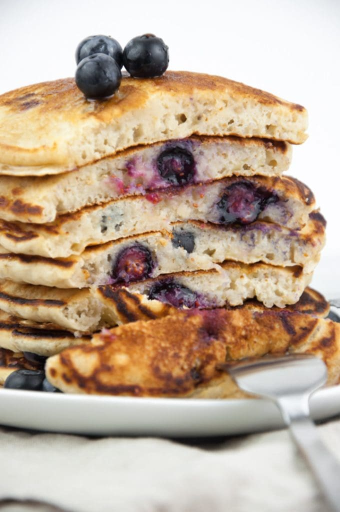 cut into a stack of fluffy vegan blueberry pancakes