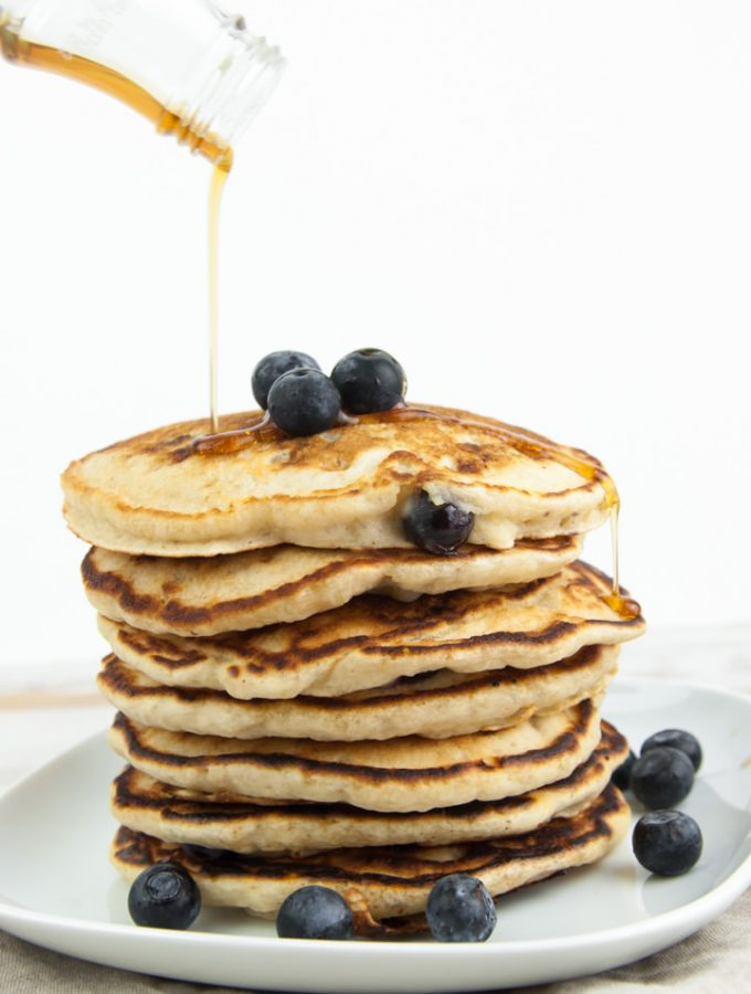a stack of fluffy vegan blueberry pancakes drizzled with maple syrup
