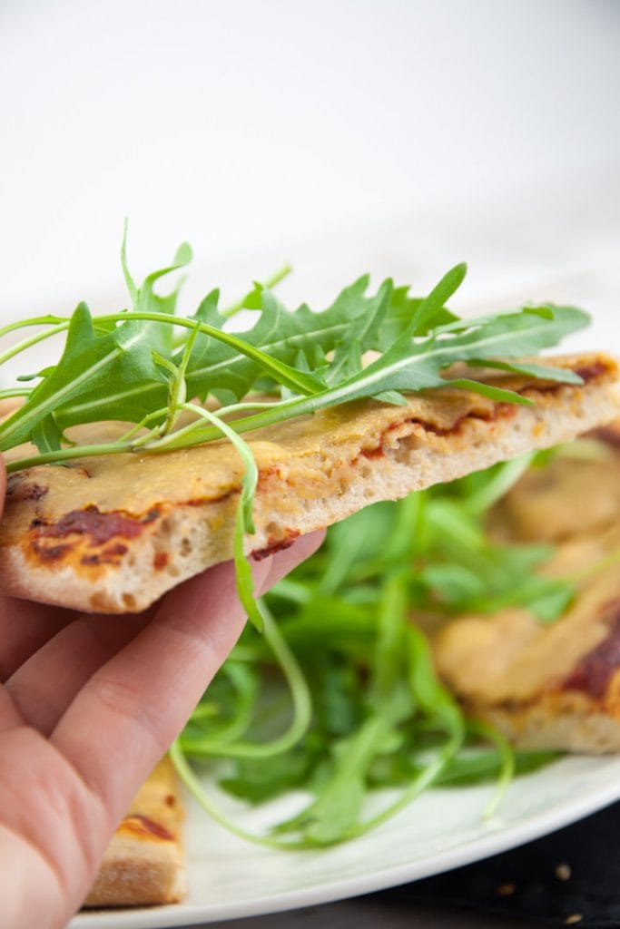 A slice of Vegan Cheese Pizza with arugula