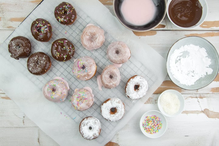 donut glazing station with chocolate, powdered sugar, sprinkles, coconut and pink glaze