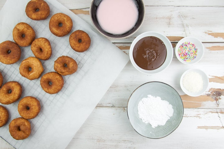 donut glazing station with chocolate, powdered sugar, sprinkles, coconut and pink glaze