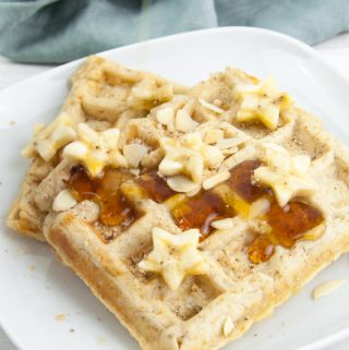 Vegan Banana Bread Waffles topped with maple syrup, banana slices, toasted almond slices and hazelnut meal