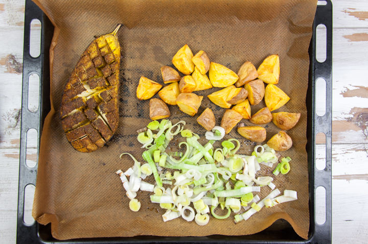 oven-roasted eggplant, potatoes and leek on baking tray