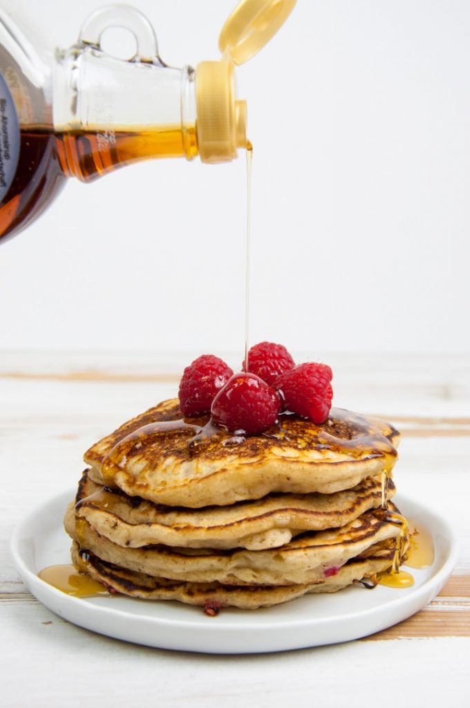 pouring maple syrup over vegan raspberry pancakes