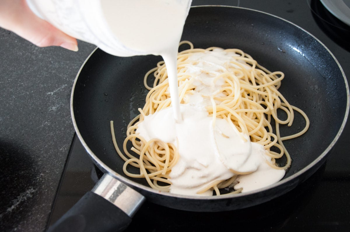 combining spaghetti and cashew sauce