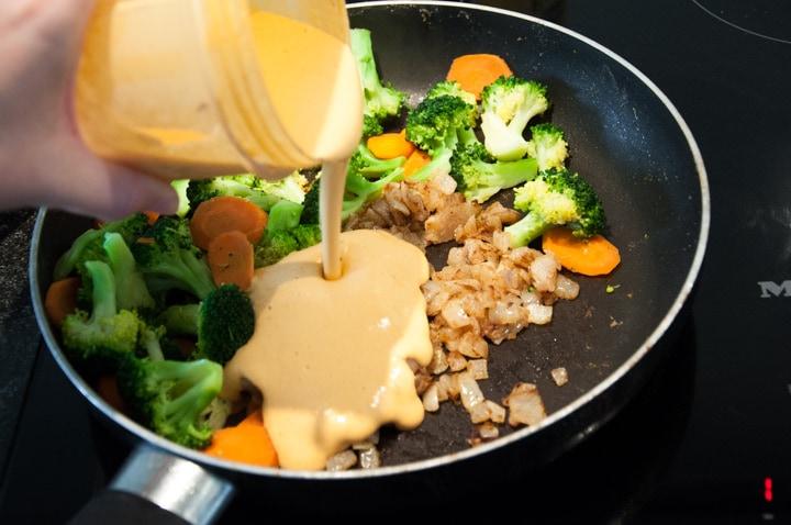 adding cashew sauce to veggies