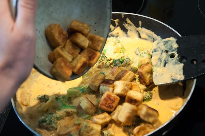 adding tofu to cashew curry