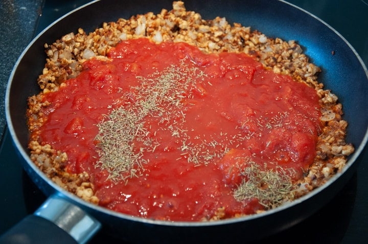 adding diced tomato to tempeh bolognese sauce