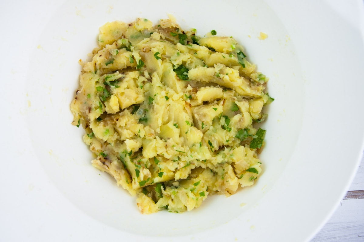 potatoes, onions, garlic, parsley, salt mixed in a bowl