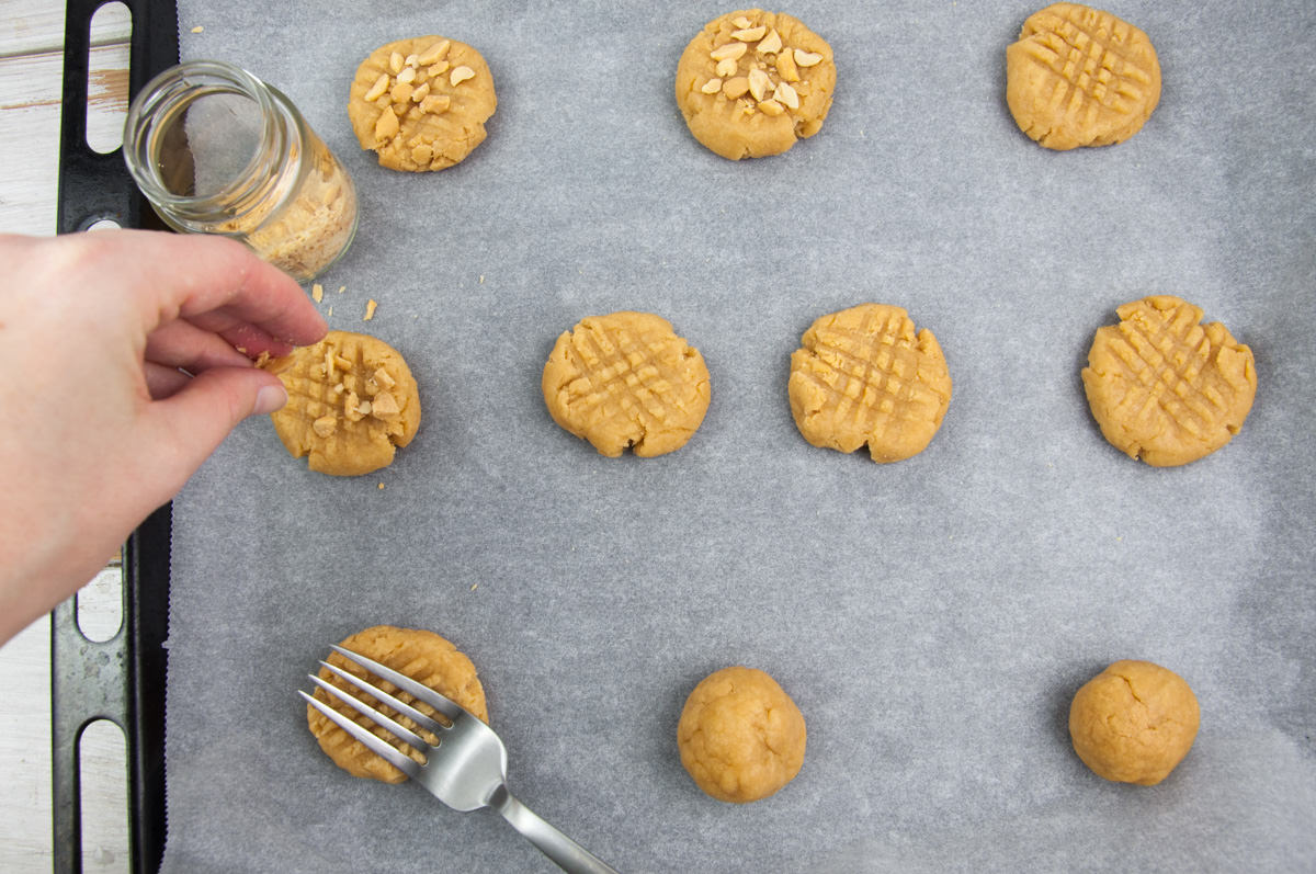 topping peanut butter cookies with salted peanuts