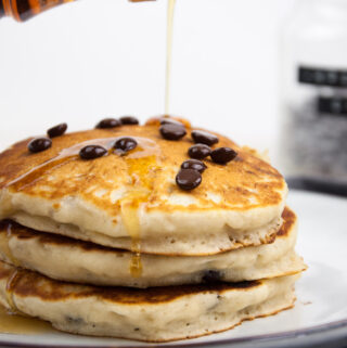 Vegan Chocolate Chip Pancakes drizzled with maple syrup