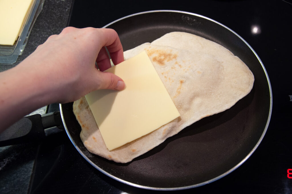 naan in a pan with a slice of cheese