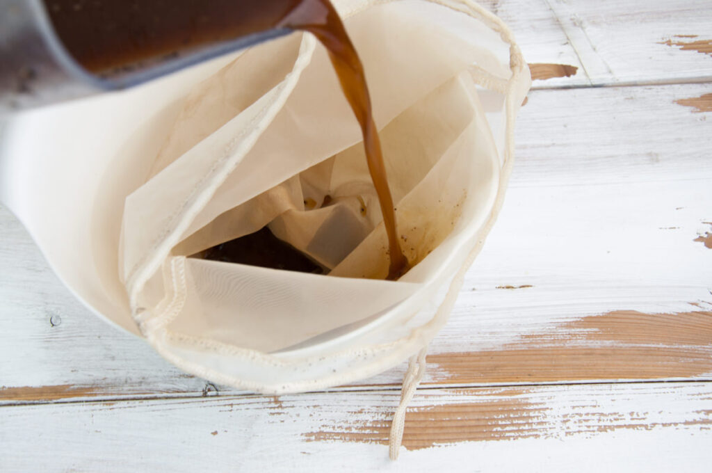 pouring coffee in nut milk bag